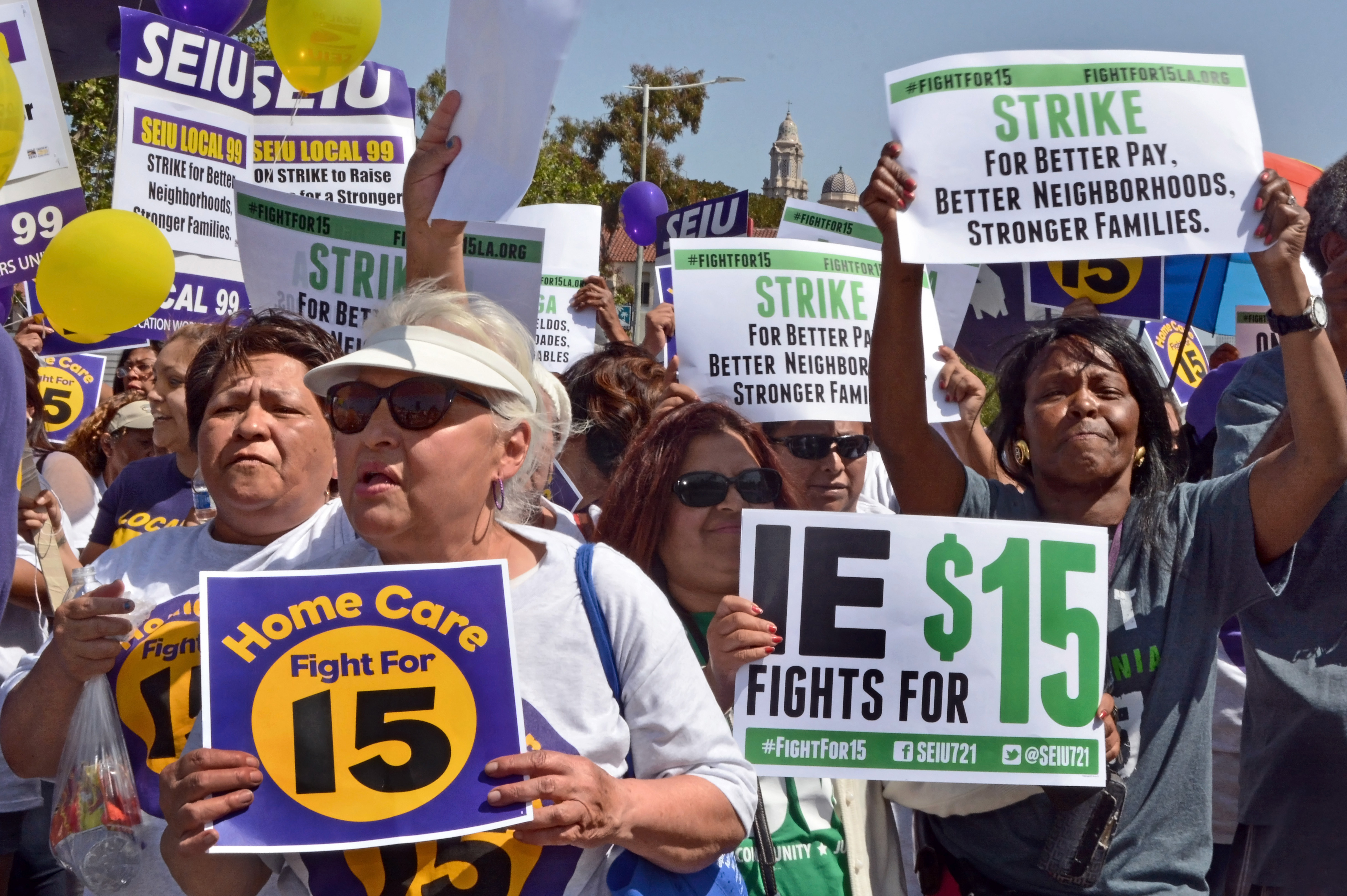 Protestors hold signs advocating raising the minimum wage at during a rally in Los Angeles on April 15, 2015.